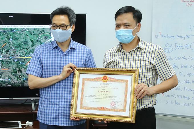 Phó Thủ tướng Vũ Đức Đam (trái) trao bằng khen cho anh Nguyễn Thế Trung. Ảnh. ĐN