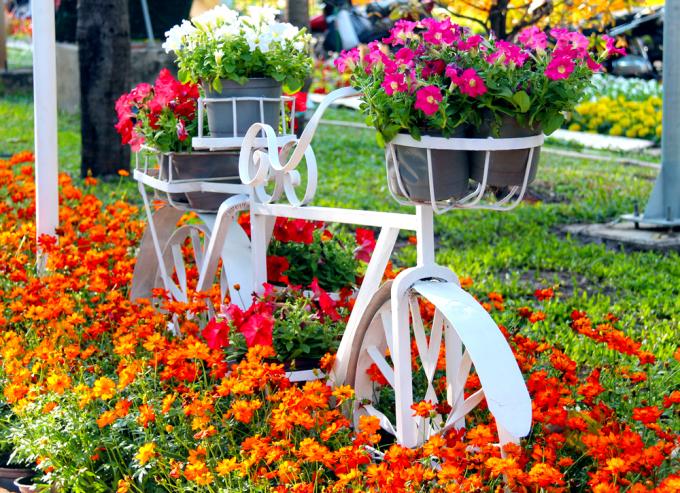 """<p class=""""Normal""""> Mô hình chiếc xe đạp chở đầy hoa lọt thỏm giữa con đường màu sắc tạo vẻ bình yên.</p>"""