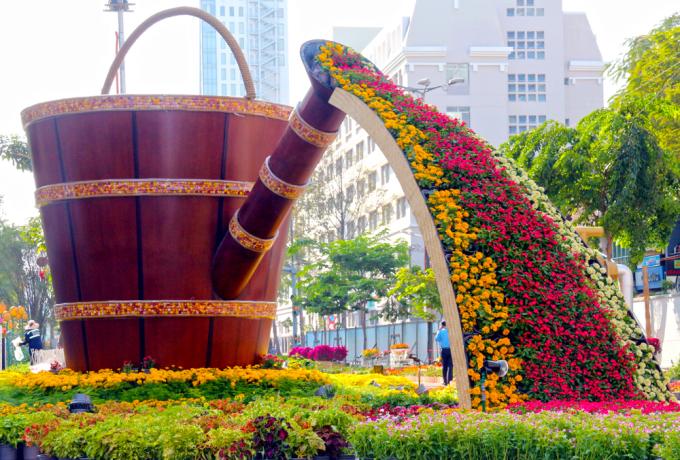 """<p class=""""Normal""""> Dòng """"suối hoa"""" chảy ra từ một chiếc bình khổng lồ làm bằng gỗ đặt giữa đường hoa.</p>"""