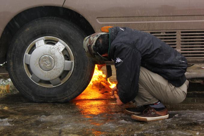"""<p class=""""Normal""""> Chiếc xe để ngoài trời vì quá lạnh máy không thể khởi động. Tài xế phải dùng đuốc """"đốt"""" gầm làm nóng nhiên liệu rồi mới khởi động được xe.</p>"""