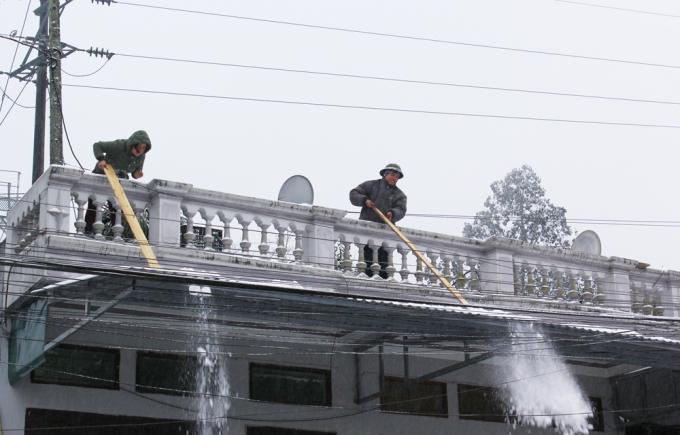 """<p class=""""Normal""""> Tuyết rơi dày đặc trên mái nhà khiến người dân phải thường xuyên gạt xuống. Có gia đình còn dùng vòi phun nước nóng lên mái nhà với mục đích làm tuyết nhanh tan.</p>"""