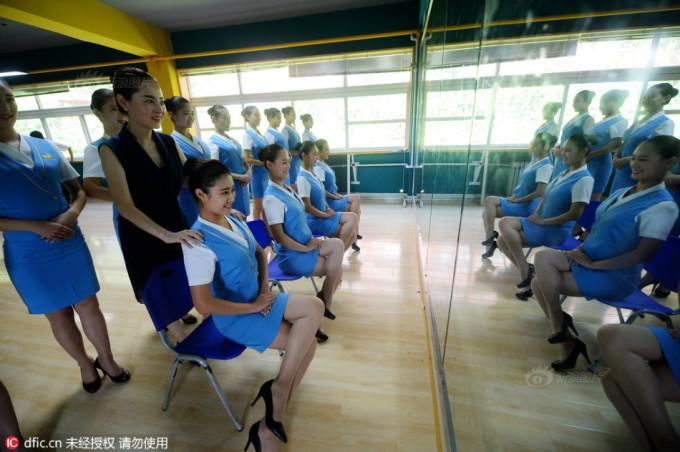 """<p class=""""Normal""""> Giảng viên chỉnh dáng ngồi cho học viên trước gương.</p> <p class=""""Normal""""> Các cô gái mặc đồng phục váy ngắn màu xanh, đi tất da chân, giày cao gót để luyện tư thế đứng, ngồi và cách cười. Thời gian luyện tập ít nhất 4 tiếng một ngày.</p>"""