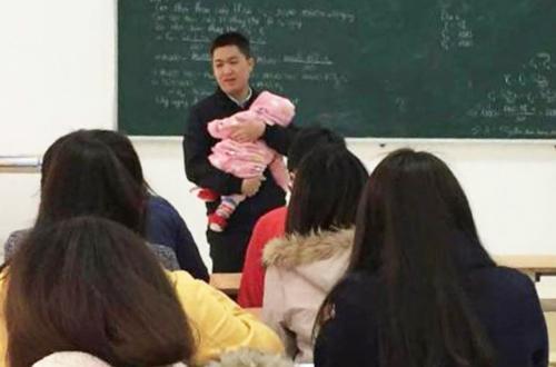 Giảng viên Nguyễn Văn Kết (Cao đẳng Công nghệ và Thương mại Hà Nội)bế con cho sinh viên làm bài thi. Ảnh: NVCC.