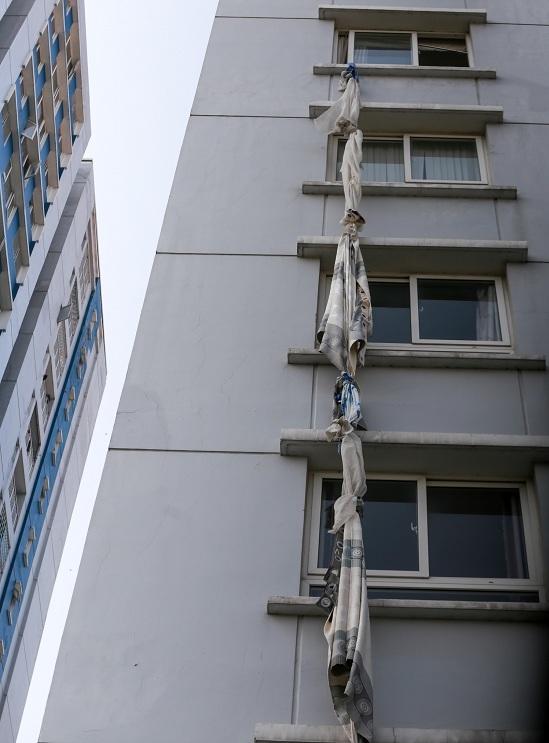 """<p class=""""Normal""""> Quanh chung cư, nhiều người dùng chăn mền, khăn rèm buộc với nhau treo trên ban công để tìm cách thoát hiểm.</p>"""