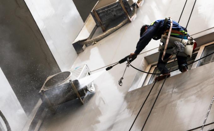 """<p class=""""Normal""""> Toà nhà gồm ba block cao từ 14 đến 20 tầng. Hàng ngày, công nhân đu dây để rửa sạch, sơn lại tường các tầng bị ám khói đen.</p>"""