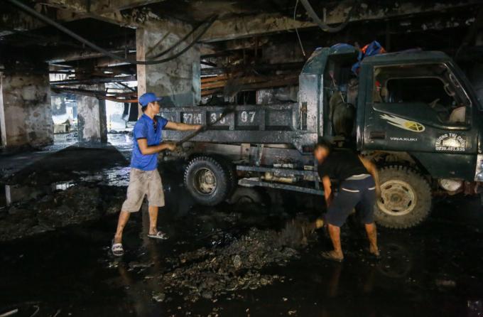"""<p class=""""Normal""""> Nhóm công nhân vệ sinh cho xe tải vào tầng hầm hốt rác thải, xà bần, lớp tro bụi... """"Nhóm tôi khoảng chục người, liên tục làm mấy ngày nay. Xà bần ở đây lẫn hóa chất nước thải nên rất bẩn, chắc phải dọn vài ngày nữa mới xong"""", anh Phú cho biết.</p>"""
