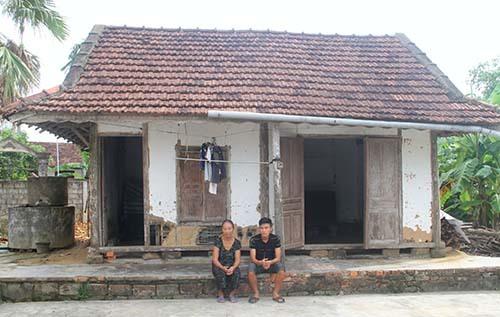 Phương và bà ngoại bên căn nhà vách đất ọp ẹp. Ảnh: Đức Hùng