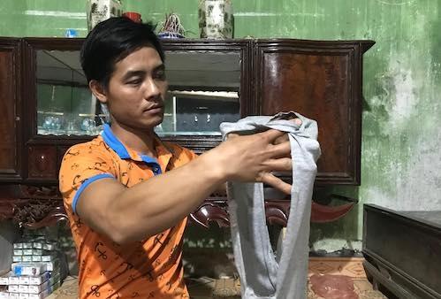 Anh Nguyễn Văn Doanh và chiếc áo bị xé rách của cháu mình. Ảnh: Dương Tâm