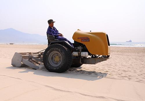 Công nhân điều khiển máy sàng cát lấy rác trên bãi biển Đà Nẵng. Ảnh: Nguyễn Đông.