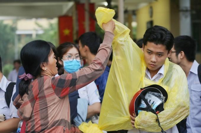 """<p class=""""Normal""""> Bà Hạnh (quận Thủ Đức) vào tận sân trường mặc áo mưa cho con. """"Chỉ sợ cháu ra ngoài dãi mưa lại ốm, ảnh hưởng tới thi cử"""", bà Hạnh nói.</p>"""