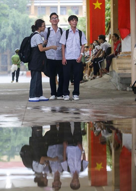 """<p class=""""Normal""""> Gầnhai tiếng sau khi hết giờ làm bài môn Toán, vẫn còn nhiều thí sinh trú ở cổng trường THPT Hiệp Bình do không mang áo mưa.</p>"""