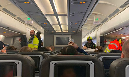 Các nhân viên của dịch vụ hỗ trợ khẩn cấp có mặt trên chuyến bay của American Airlines hôm 21/10. Ảnh: Twitter/Katie Phillips.