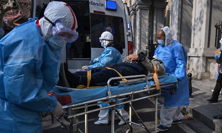 Nhân viên y tế đưa bệnh nhân nghi mắc viêm phổi cấp do virus corona rakhỏi một chung cư tại Vũ Hán, Trung Quốc ngày 30/1. Ảnh: AFP.
