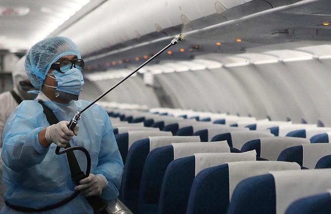Nhân viên y tế khử trùng máy bay của VNA ngày 4/2. Ảnh: Ngọc Thành