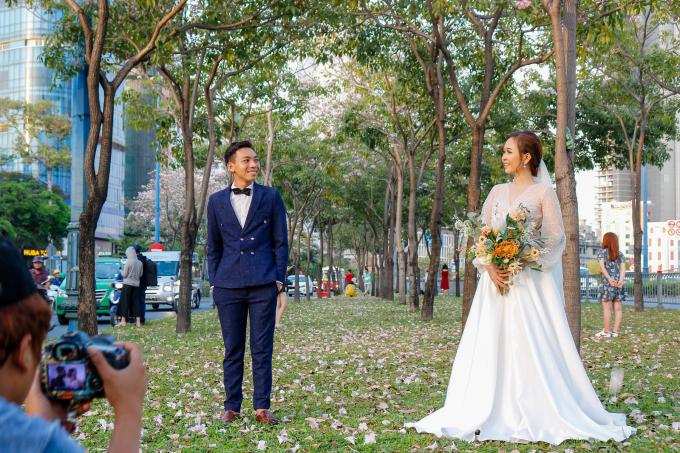 <p> Đôi bạn trẻ chụp ảnh cưới giữa đường hoa kèn hồng ở quận 1.</p>