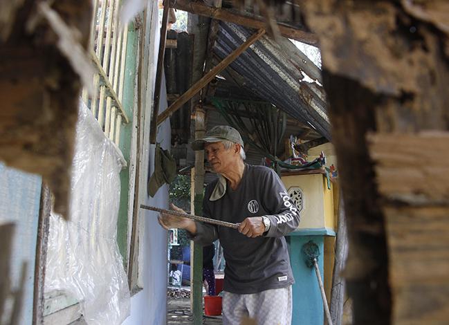 Ông Kiên tự tay tháo dỡ căn nhà mình sinh sống 30 năm qua. Ảnh: Võ Thạnh