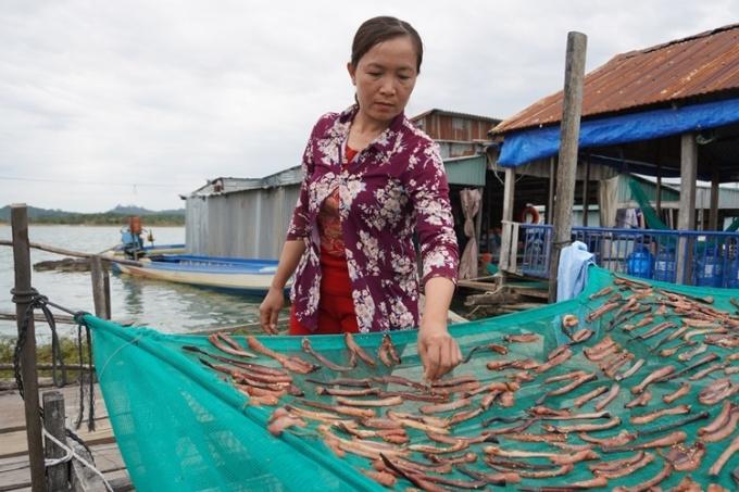 Chị Nhung phơi cá trê, đóng gói bán cho khách du lịch. Ảnh: Trần Hóa.