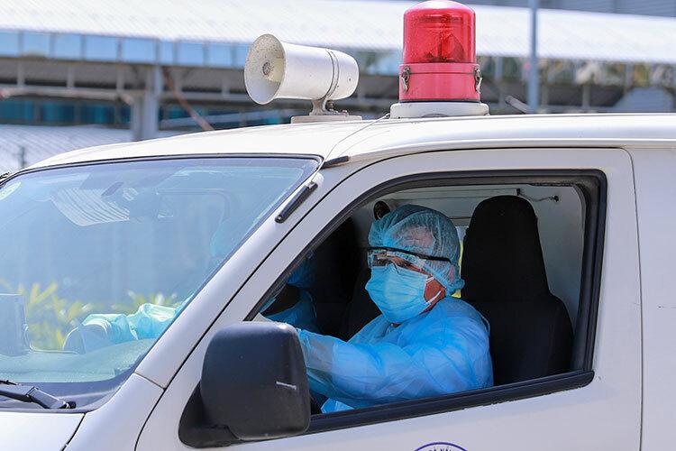 Nhân viên y tế bịt kín đồ bảo hộ khi đưa người nghi nhiễm virus corona từ sân bay về Bệnh viện Phổi. Ảnh: Nguyễn Đông.