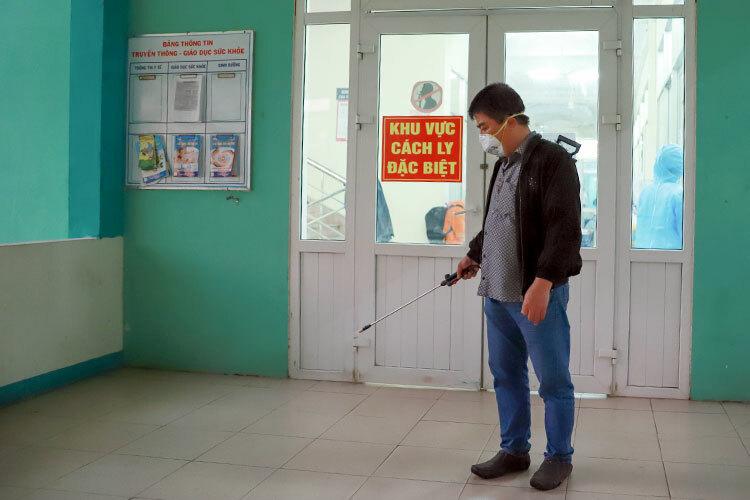 Nhân viên y tế phun thuốc tiêu độc khử trùng bên ngoài khu cách ly tại Bệnh viện phổi, chiều 24/2. Ảnh: Nguyễn Đông.