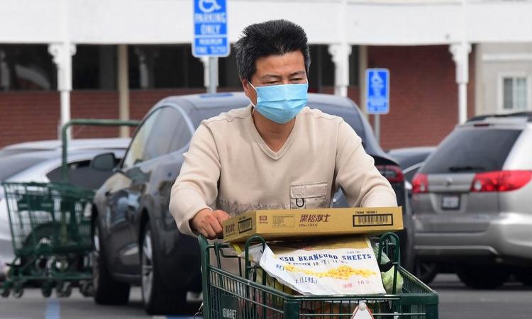Một người đeo khẩu trang khi mua hàng tại bang california hôm 27/2. Ảnh: AFP.