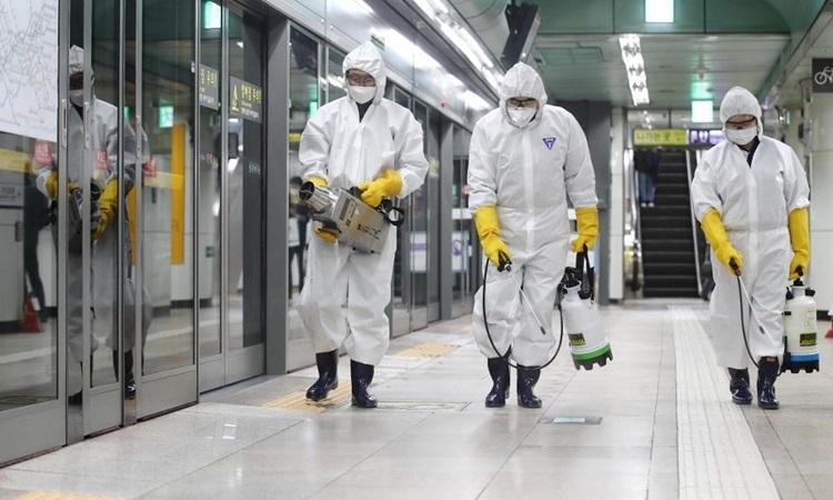 Công nhân mặc đồ bảo hộ phun thuốc khử trùng một nhà ga ở thủ đô Seoul của Hàn Quốc hôm 28/2. Ảnh: AFP.