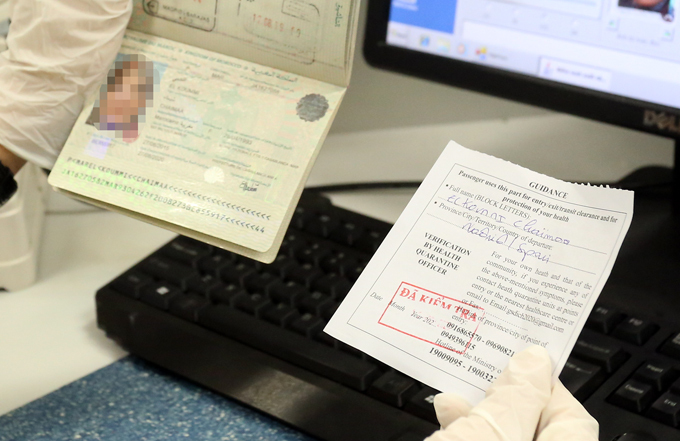 Công ankiểm tra phiếu khai báo y tế được kiểm tra và đóng dấu của khách nước ngoài hôm 11/3. Ảnh: Bá Đô