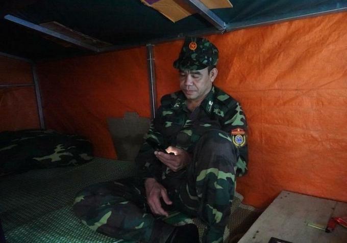 Thiếu tá, quân nhân chuyên nghiệp Trần Đức Thọ ngồi trong lán tạm, xung quanh lót nhiều tấm bìa cát tông để thấm nước giột, tranh thủ lúc rảnh rỗi gọi điện về cho vợ con ở Thái Bình. Ảnh: Hoàng Thuỳ