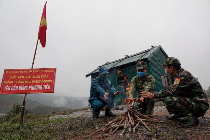 Thiếu tá Nguyễn Đắc Đạt (giữa) và đồng đội liên tục phải đốt lửa để sưởi ấm vàhong khô quần áo trước căn nhà tạm được huyện hỗ trợ tiền xây dựng, sau hai lần lều dã chiến bị gió thổi bay xuống vực. Ảnh:Hoàng Thuỳ