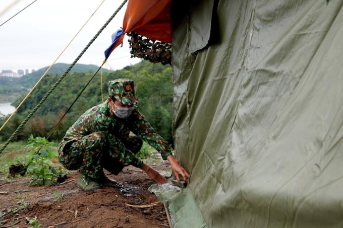 Trung tá, quân nhân chuyên nghiệp Bùi Văn Bách, 51 tuổi, đang gia cố lại lán dã chiến. Ảnh: Hoàng Thuỳ