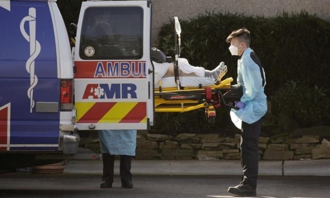 Nhân viên y tế Mỹ đưa người nhiễm nCoV lên xe cứu thương bên ngoài trung tâm chăm sóc người cao tuổi ở bang Washington hôm 4/3. Ảnh: Reuters.