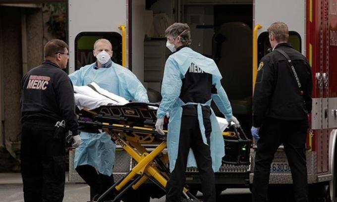 Nhân viên y tế Mỹ di dời bệnh nhân Covid-19 lên cáng cứu thương ở bang Washington đầu tháng này. Ảnh: Reuters.