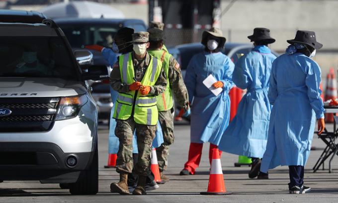 Nhân viên y tế và binh sĩ tại điểm xét nghiệm do Vệ binh Quốc gia bang Florida dựng tại bãi đỗ xe của sân vận động Hard Rock, thành phố Miami Gardens ngày 30/3. Ảnh: AFP.