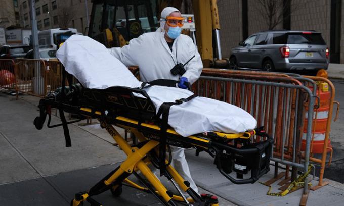 Một tài xế xe cứu thương cất xe đẩy bên ngoài một bệnh viện ở thành phố New York, Mỹ hôm 31/3. Ảnh: AFP.