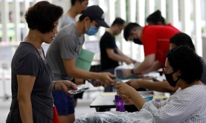 Người dân Singapore nhận khẩu trang tái sử dụng miễn phí từ chính phủ tại một trung tâm cộng đồng ngày 5/4. Ảnh: Reuters.