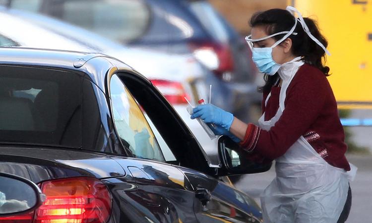 Một nhân viên y tế lấy mẫu xét nghiệm nCoV cho nhân viên Dịch vụ Y tế Quốc gia Anh ở trạm lưu động trong bãi đỗ xe ở Wembley, tây bắc London ngày 4/4. Ảnh: AFP.