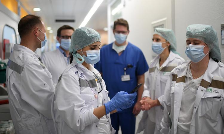 Các bác sĩ Pháp thảo luận với một bác sĩ Đức (thứ hai, từ trái sang) sau khi đưa bệnh nhân đến Bệnh viện Đại học Essen ngày 1/4. Ảnh: AFP.