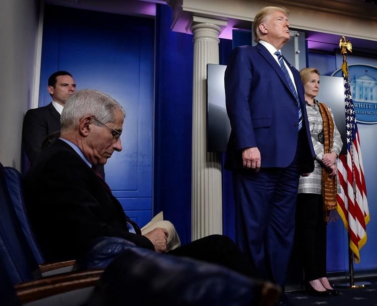Anthony S. Fauci (trái, ngồi ghế) lắng nghe Tổng thống Trump phát biểu trong cuộc họp báo ở Nhà Trắng ngày 5/4. Ảnh: Washington Post.