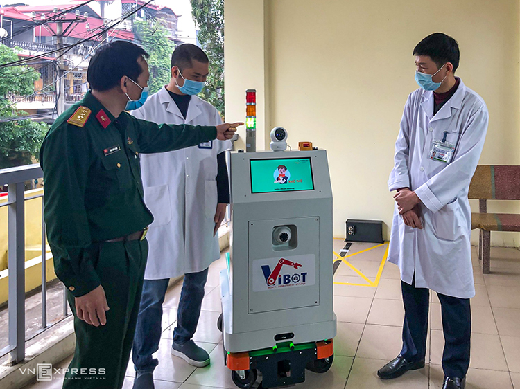 PGS.TS. Đại tá Tăng Quốc Nam, Chủ nhiệm đề tài (bìa trái) giới thiệu robot tới các bác sĩ bệnh viện Bắc Thăng Long. Ảnh: BN.