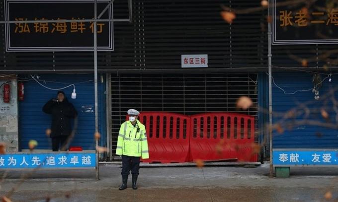 Nhân viên cảnh sát đứng gác trước chợ hải sản Hoa Nam ở Vũ Hán, ngày 10/1. Ảnh: Reuters.