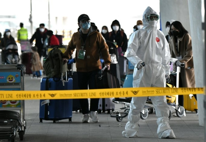 Cảnh sát mặc đồ bảo hộ hướng dẫn các công dân Hàn Quốc hồi hương ở sân bay quốc tế Incheon, Seoul, hôm 1/4 lên xe buýt. Ảnh: AFP