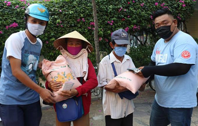 Tình nguyện viên tặng quà cho người bán vé số ở quận Ninh Kiều. Ảnh: Hưng Lợi