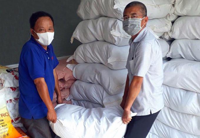 Ông Nguyên (phải) cùng cộng sự tập kết gạo để tặng cho người nghèo. Ảnh: Hưng Lợi.