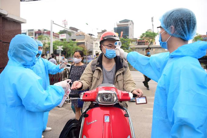 Đo thân nhiệt người ra vào bệnh viện Bạch Mai, ngày 28/3. Ảnh: Giang Huy