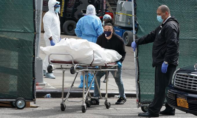 Một thi thể được đưa ra khỏi xe đông lạnh được dùng làm nhà xác dã chiến bên ngoài Bệnh viện Trung tâm Brooklyn, New York, Mỹ ngày 8/4. Ảnh: AFP.