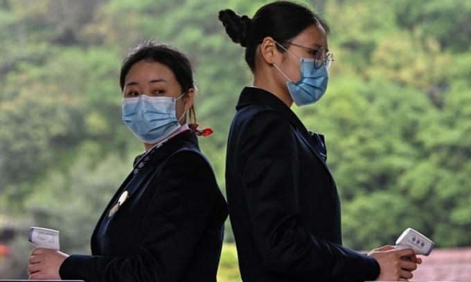 Nhân viên kiểm tra thân nhiệt tại một điểm tham quan ở Vũ Hán ngày 10/4. Ảnh: AFP.