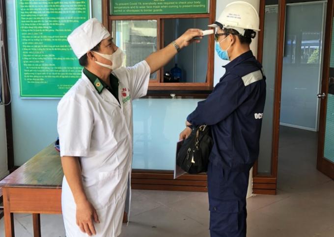 Nhân viên làm việc ở cảng Cát Lái đang được bác sĩ quân y kiểm tra thân nhiệt trước khi vào cảng. Ảnh: Hà An.