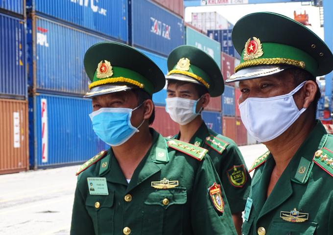 Đại úy Vũ Quốc Hội (bên trái) cùng với đồng đội kiểm tra phòng chống dịch ở cảng Cát Lái. Ảnh: Hà An.