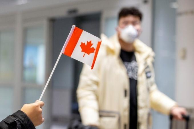 Một hành khách mang khẩu trang tại sân bay Toronto, Canada, ngày 26/3. Ảnh: Reuters.