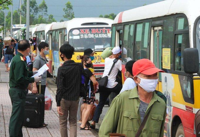 Người dân hoàn thành cách ly ở Hà Tĩnh được nhà chức trách điều xe buýt chở về quê. Ảnh: Đức Hùng