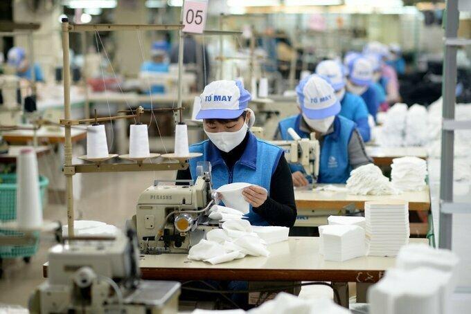 Công nhân sản xuất khẩu trang vải kháng khuẩn tại Công ty Dệt kim Đông Xuân.Ảnh: Cao Nam